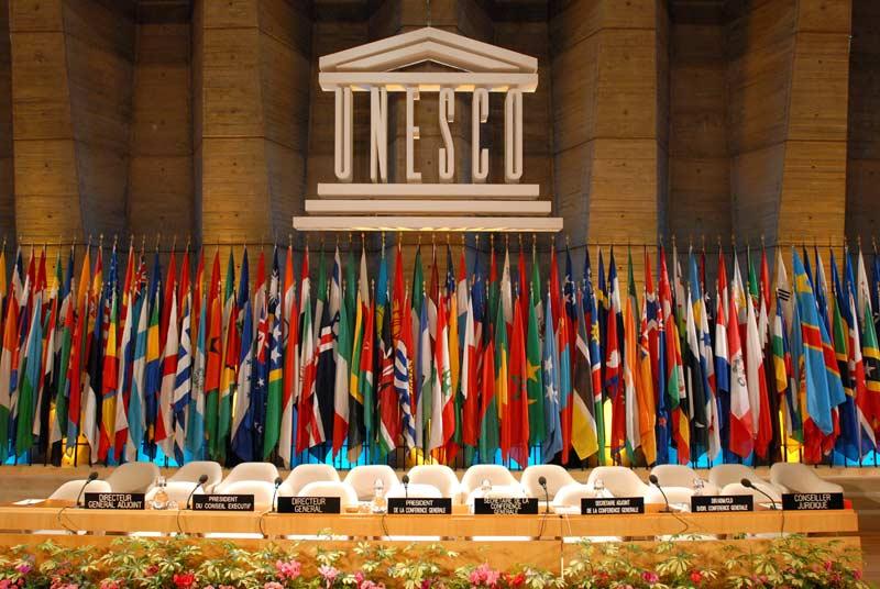 Salón plenario de la 34ª Conferencia General de la UNESCO con banderas de países de todo el mundo.