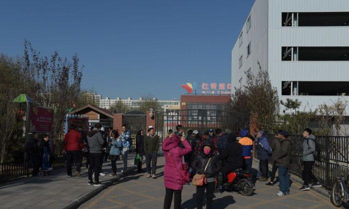 Personas frente a la puerta principal del jardín de infantes RYB Education New World en Beijing el 24 de noviembre de 2017. La policía china ha iniciado una investigación sobre el presunto abuso infantil en la institución de Beijing.