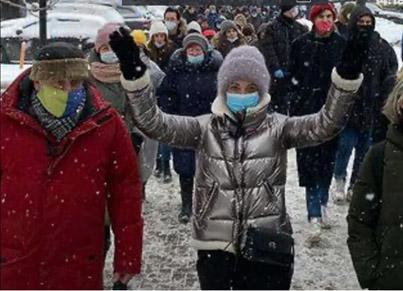 La mujer de Navalny acompañada de un activista con una máscara con los colores de la bandera ucraniana