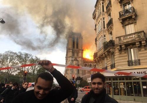 Dos musulmanes abandonan la zona de seguridad del incendio con rostros evidentes de alegría y felicidad.